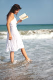 Love success. Romantic scene of a book holding woman walking the coastline royalty free stock photo