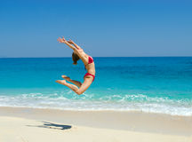 In love with the summer. Young athletic woman is doing a jump on the beach Stock Photos