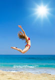 In love with the summer. Young woman in bikini is jumping at the sun Stock Image