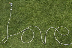Love summer hose word on lawn. Word love written in a garden hose on a lush lawn Stock Photos