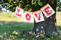 Love and summer. The word love from red letters hanging on the big tree in the summer Stock Images