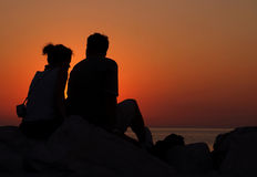 Love and sunset. A couple sitting on a rock in summer, watching the sun setting Stock Photos