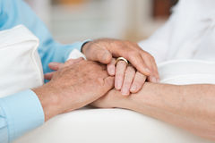Love and support. Sentimental conceptual image of love, commitment and support between two elderly people as they tenderly hold hands, close up view Stock Image