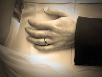 Love, support and tenderness. The grooms hand resting on the back of the bride Stock Photo