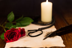 Love and sweet pain. Letter, whip, candle and rose Stock Photo