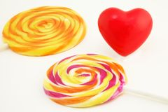 Love for Sweet Things. Positive design with two lollipops and a red heart shape Royalty Free Stock Image