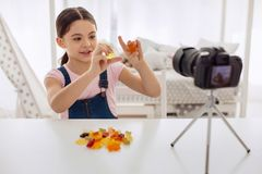 Cheerful girl reviewing gummy bears and recording it Stock Photo