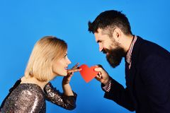 Love symbol concept. Girl and bearded man with concentrated faces. Love symbol concept. Girl and bearded men with concentrated faces share paper heart card for royalty free stock image