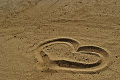 Love symbol drawn in the sand. Into the right bottom of the frame royalty free stock photography