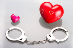 Love symbol in handcuffs. Two hearts with handcuffs as a love symbol Stock Photos