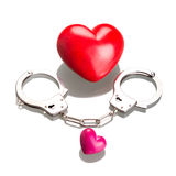 Love symbol in handcuffs over white. Two hearts with handcuffs as a love symbol Stock Photography