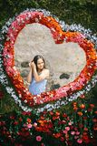 Love symbol, romance. Young girl pose in floral heart, spring. Happy valentines day concept. Child smile in flower frame on natural background. Flower stock photo