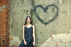 Love symbol of spray paint. Valentines day holiday celebration concept. Girl posing with heart graffiti on grey wall. Woman wearing black dress on grunge stock photography