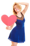 Love symbol. woman holds big red heart. Red heart card. Love symbol. Beautiful woman holding valentine day symbol. Cute crazy blonde girl in blue dress royalty free stock photography