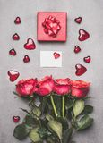 Love symbols composing with red gift box, ribbon, roses bunch , blank white paper card and heart, top view. Stock Photo