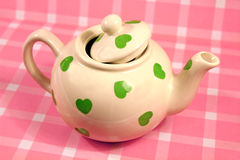 Love tea. Photo of a country pink gingham table cloth with pretty white teapot with green lovehearts Stock Images