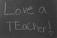 Love a Teacher!. A third grader's hand writing on an old school black board Stock Image