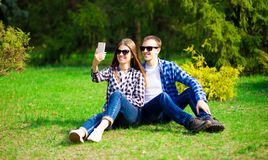 Love, technology, relationship, family and people concept - happy smiling young couple taking selfie in summer park. Happy together royalty free stock photography