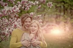 Love and tenderness. Beautiful young loving couple embracing in blossom spring garden. Romantic dating Stock Photos