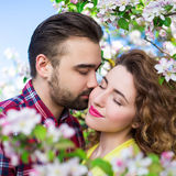 Love and tenderness - close up portrait of beautiful couple kiss. Ing in blooming summer garden Stock Photos