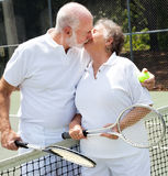 Love on the Tennis Court. Romatic senior couple kissing on the tennis court Stock Images