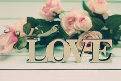 Love text against defocused vintage roses background Stock Photos