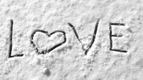 Love text Hearts on snow hand drawing symbol romantic wintertime. Hearts on snow hand drawing symbol romantic wintertime ice cold surface Stock Photo