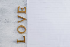 Love text and notepad. Love background, wooden love text and white paper sheet on wood texture background Royalty Free Stock Images