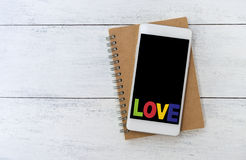 Love text over smartphone Royalty Free Stock Photos