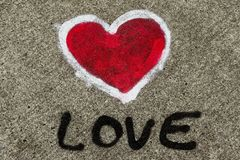 Love text and red heart shape with white outline painted sprayed on massive concrete wall. Creative concept symbolic for love. Romance, passion, couple royalty free stock images