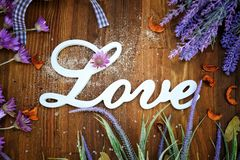 Love text on a rustic wooden background with lavender. And meadow herbs royalty free stock photo