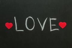 Love text written on chalkboard. Royalty Free Stock Image