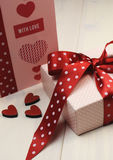 Love theme ft card with pink gift and red polka dot ribbon and hearts. Vertical. Stock Photography