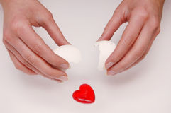Love is there!. Red heart falling out of a broken egg from a female hands stock photo