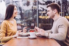 Sweet adorable couple has date. Love time. Happy merry young couple eating salads while laughing and sitting in front of each other stock photo