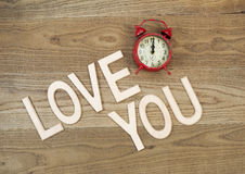 Love is timeless. Overhead view of an old table top alarm clock and large wooden letters spelling out Love You on rustic wood stock image