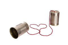 Love tin can phone. Old tin cans connected with a heart shaped wire Royalty Free Stock Photo