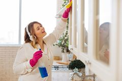 Positive nice woman cleaning cupboards in the kitchen