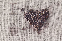 Love to coffee - Burlap texture with beans heart shape Stock Images