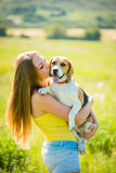 Love to dog. Teenage girl kissing her beagle dog - outdoor in nature Stock Photos