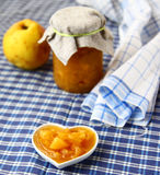Love to the quince jam. Jar of the quince jam and wall outlet in form heart with portion of jam Stock Photography