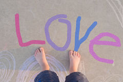 Love Toes. Precious toddler toes on a pavement with love written on the pavement Royalty Free Stock Photo