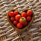 Love Tomatos! In Wooden Bowl. Tomatos in Wooden Heart Shaped Bowl, Wicker Background stock photos