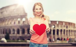 Happy woman or teen girl with red heart shape. Love, travel, tourism, valentines day and people concept - smiling young woman or teenage girl with blank red Stock Images