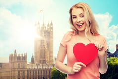 Happy woman or teen girl with red heart shape. Love, travel, tourism, valentines day and people concept - smiling young woman or teenage girl with blank red Royalty Free Stock Photo