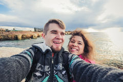 We love traveling. Adventure Selfie. Caucasian young couple taking selfie while they walking on mountains near the sea. We love traveling. Adventure Selfie Stock Image