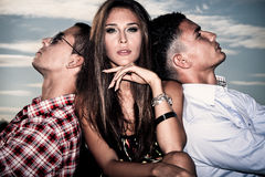 Love triangle. One young women and two young men, love triangle, outdoors shot