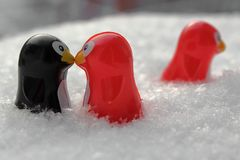 Love triangle or being third wheel. Having affair, infidelity or cheating concept. Unrequited love concept. Valentine`s day concept. Three toy penguins in the stock photo