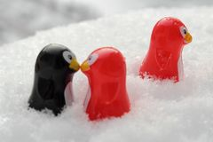 Love triangle or being third wheel. Having affair, infidelity or cheating concept. Unrequited love concept. Valentine`s day concept. Three toy penguins in the stock photography