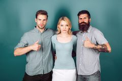 Love triangle concept. Blonde girl and two guys in casual clothes looking at the camera. royalty free stock images